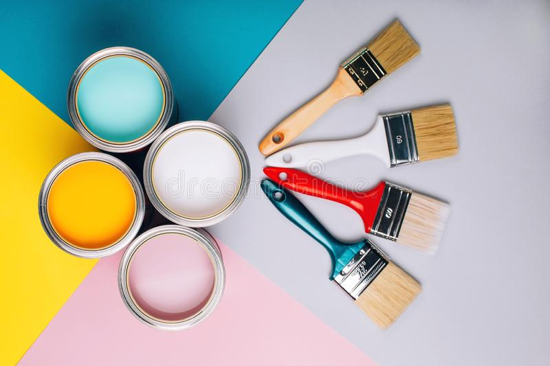 Four open cans of paint with brushes on bright background. stock image