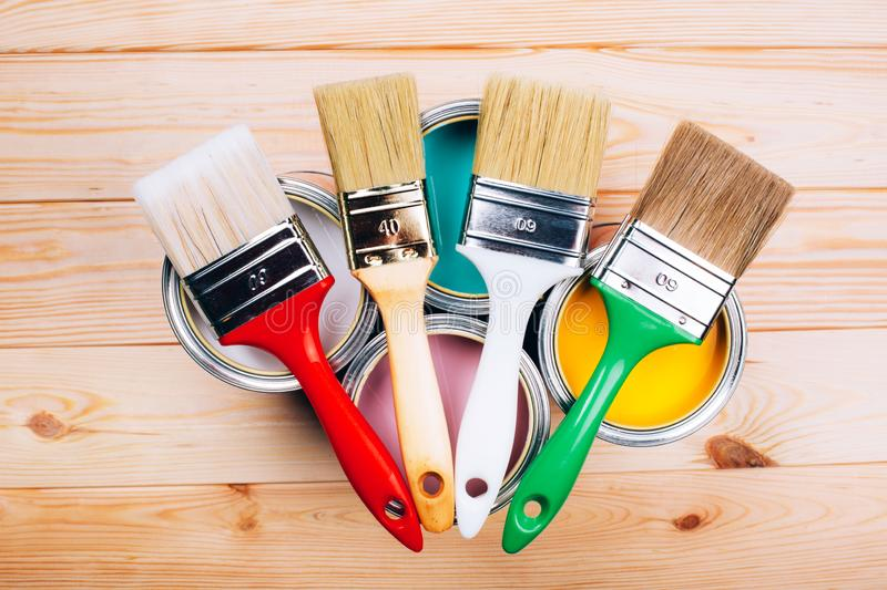 Four open cans of paint with brushes on them on wooden natural background. royalty free stock photos