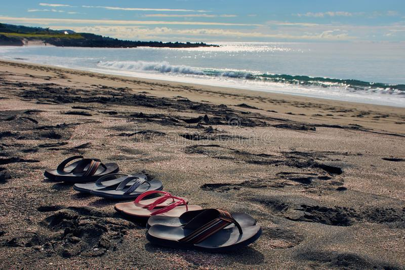 Four pair of flip flops at the beach. Family pair of flip flops standing on the beach near Ponta Delgada on the Azores with view to Atlantic Ocean royalty free stock image