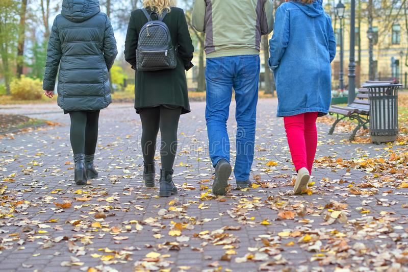 Four pairs of legs male and female go on autumn leaves stock photo