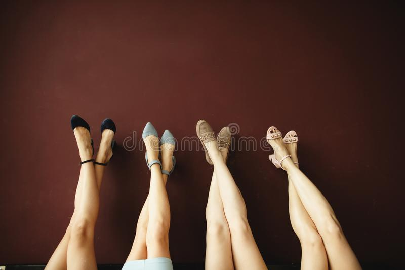 Four pairs of women`s legs in the shoes, upside down on the background of a brown wall. Space for text stock photo