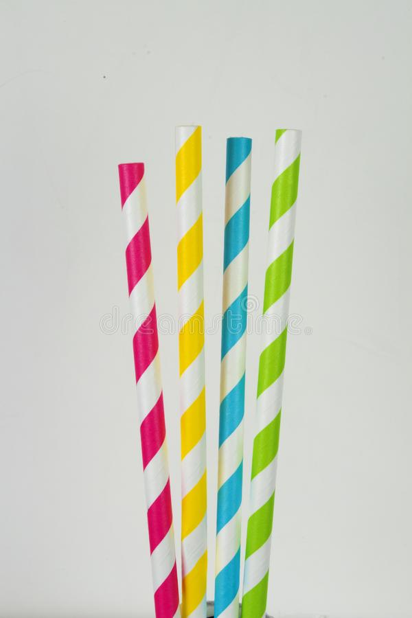 Four paper straws in a vertical format on a white background. Four multi-colored striped paper straws in a vertical format against a white background stock image