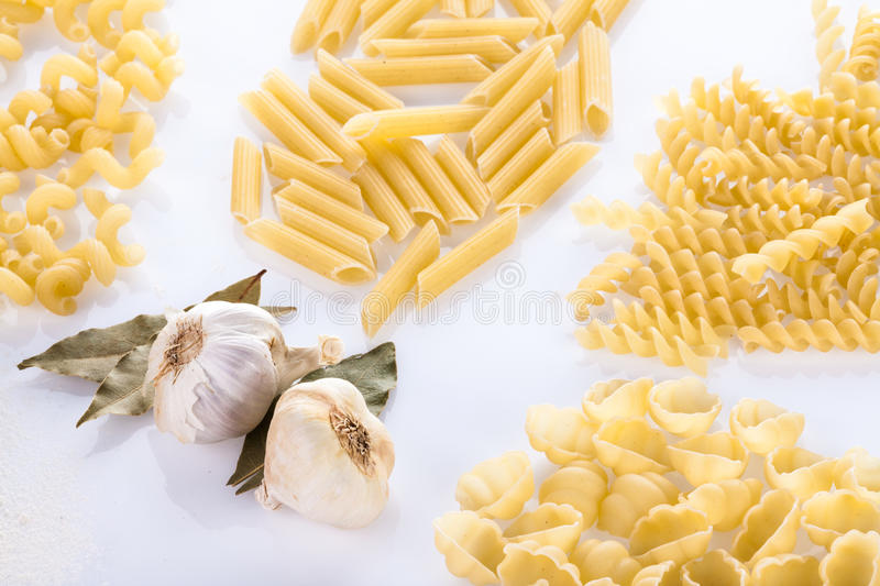 Four pasta types with two cloves of garlic stock photos