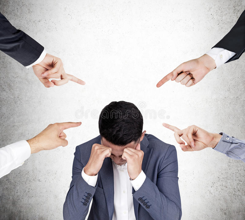 Four people are blaming a stressed Asian businessman. Four hands pointing at Asian businessman who is stressed out. Concept of blaming and shaming stock photo