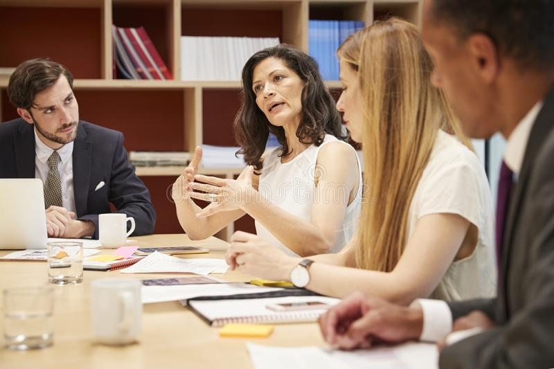 Four people at a business boardroom meeting royalty free stock image