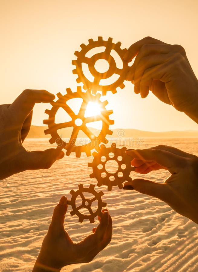 Four people hold gears on sunset background. stock photos