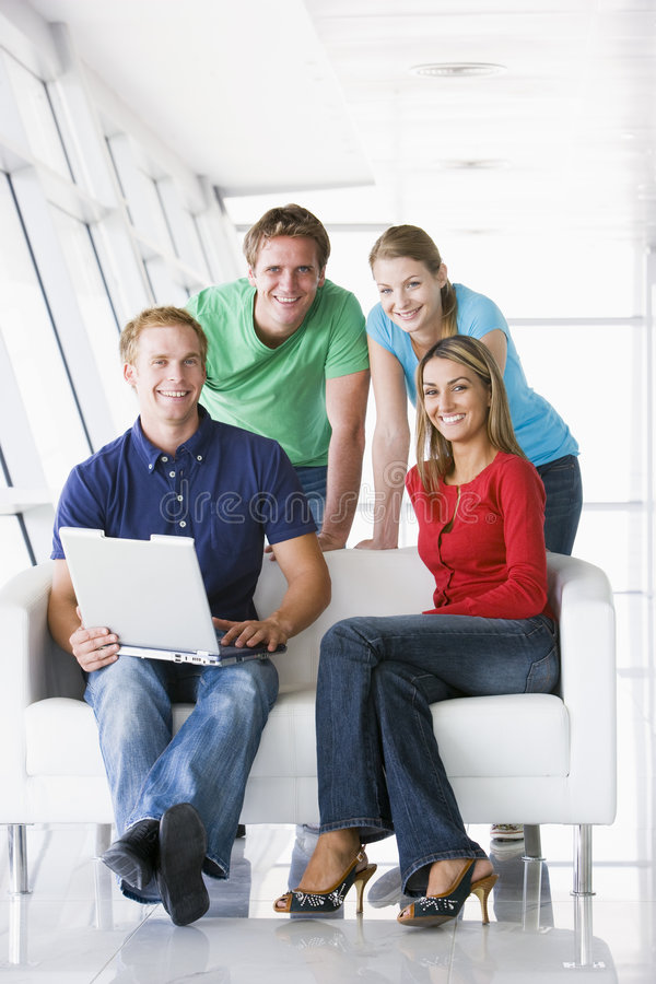 Four people in lobby with laptop smiling royalty free stock image