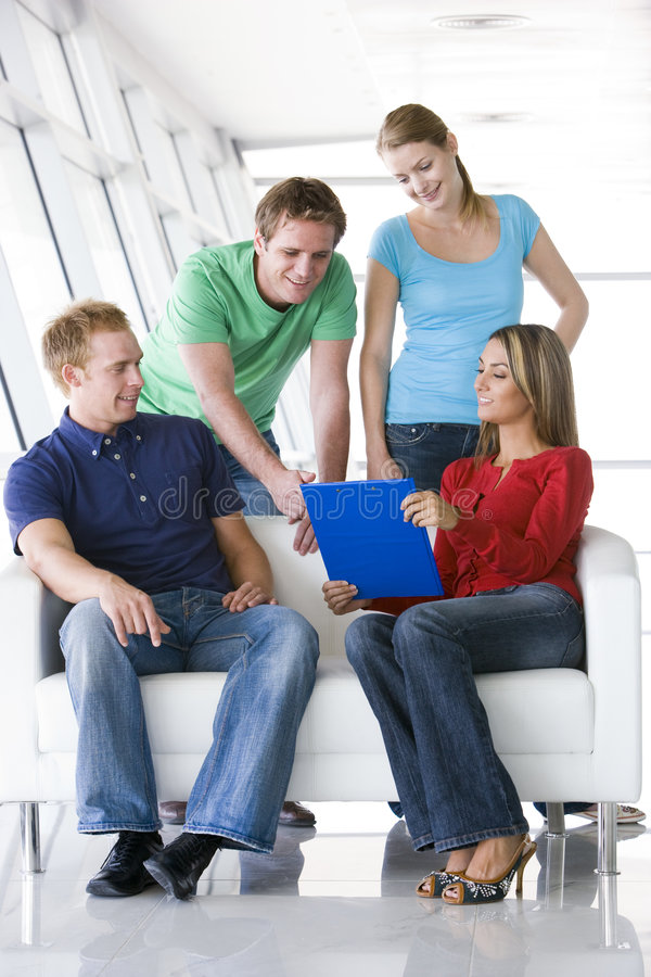 Four people in lobby pointing at clipboard smiling stock photo