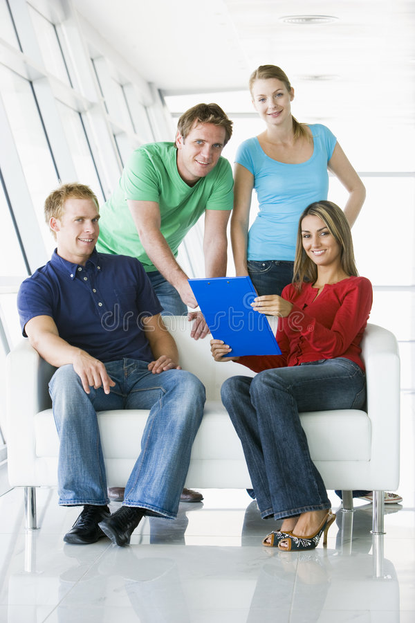 Four people in lobby pointing at clipboard smiling stock photos