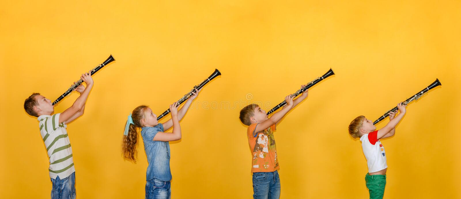 Four people, a musician, stand in a row and play clarinets, photos of children on a yellow background royalty free stock photos