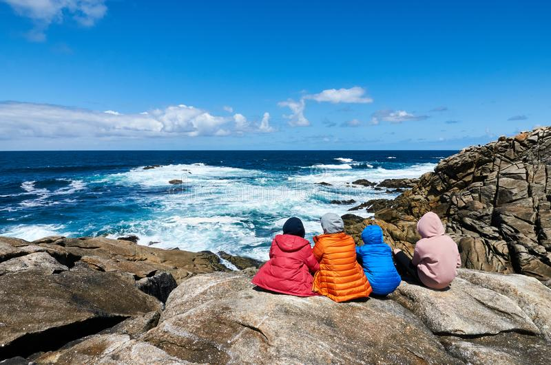 Four people staring at the sea at the Coast od Death, Laxe, Spain stock photography