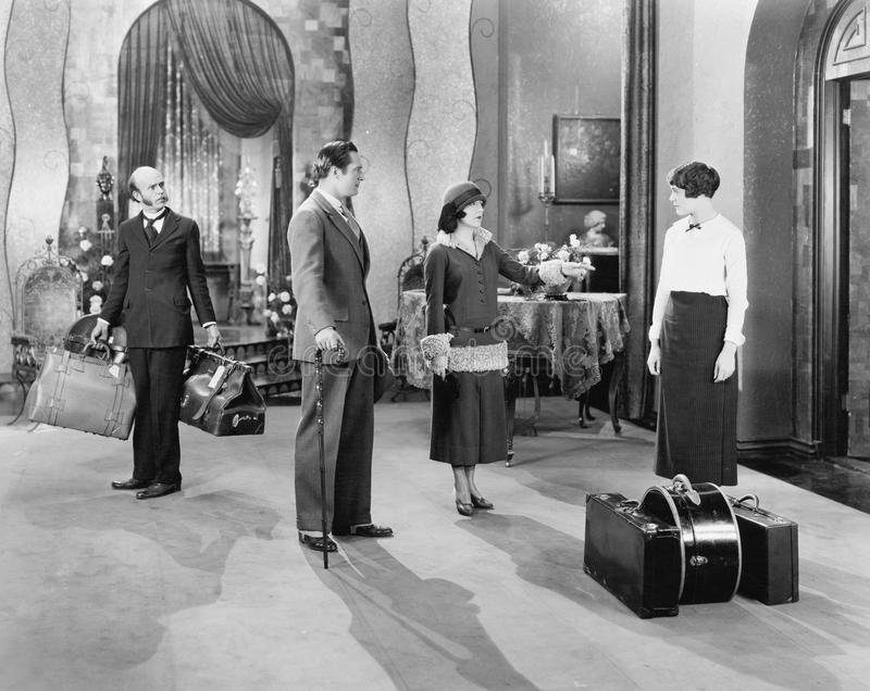 Four people standing in a the lobby of a hotel with luggage. (All persons depicted are no longer living and no estate exists. Supplier grants that there will be royalty free stock photos