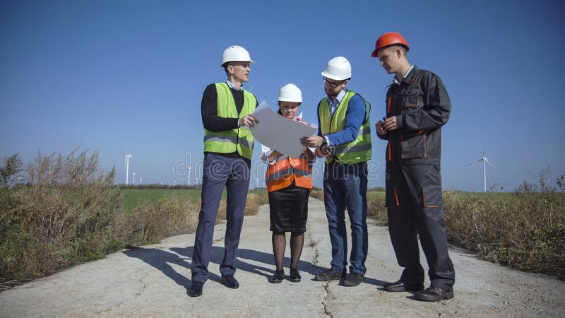 Four people standing in open field. Four people in multicolored vests and hard hats standing in open field next to large white windmill royalty free stock photo