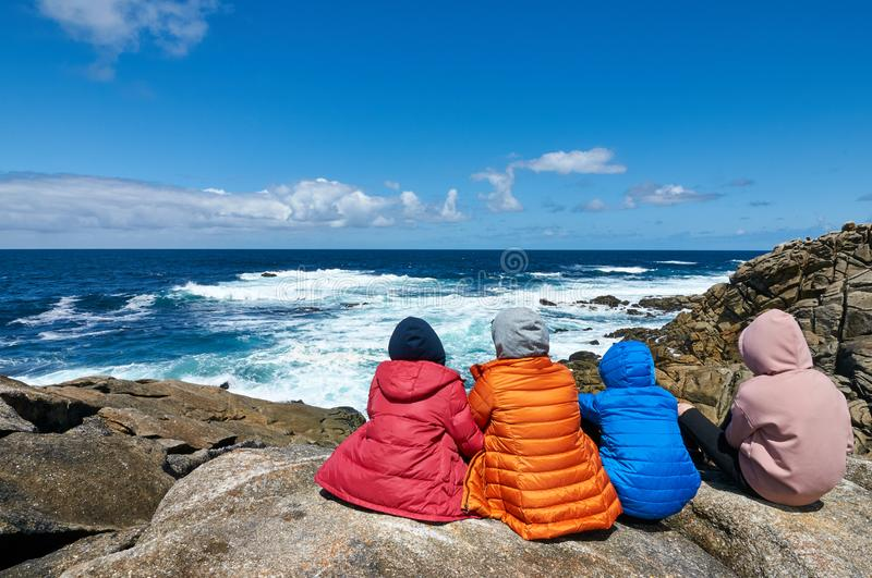 Four people staring at the sea at the Coast od Death, Laxe, Spain stock images