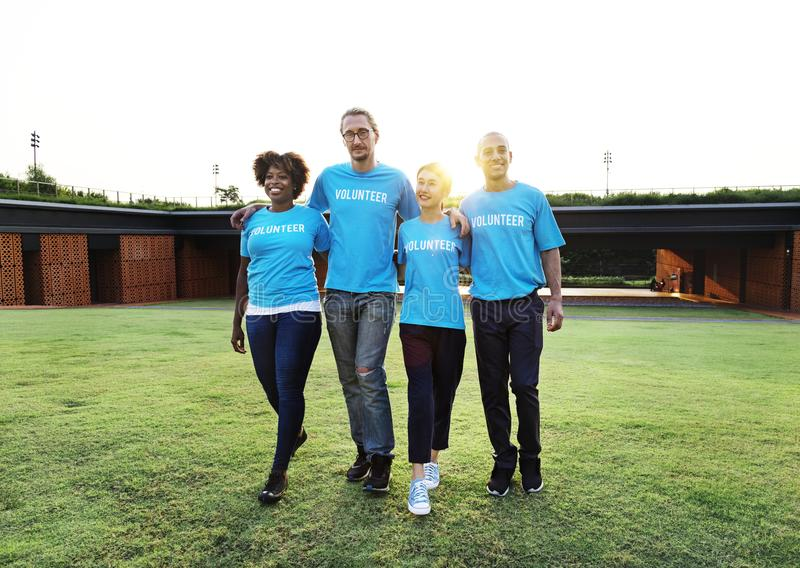 Four People Wearing Blue Crew-neck Shirts Standing on Lawn stock photography