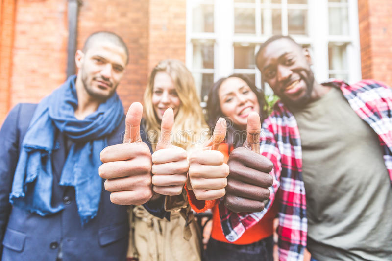 Four persons with different ethnicities showing thumbs up. Group of happy friends standing side by side, focus on the hands. Concepts of integration royalty free stock photography