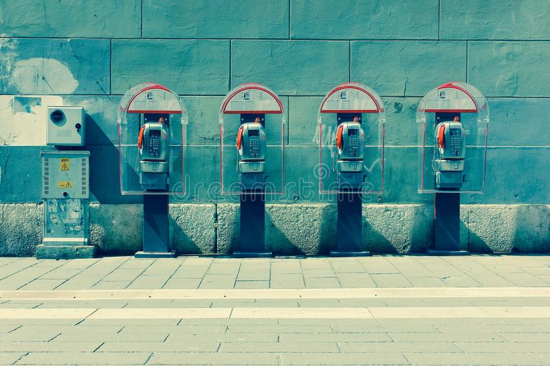 Four phone booths by the wall. Trieste, Italy stock photography
