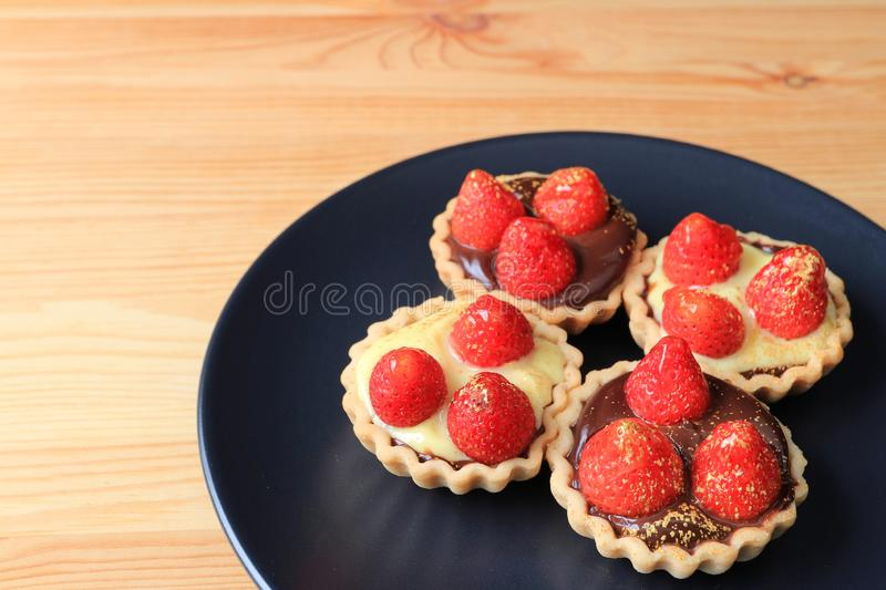 Four pieces of mini chocolate tarts topped with fresh strawberries and edible gold powder served on black plate royalty free stock photos