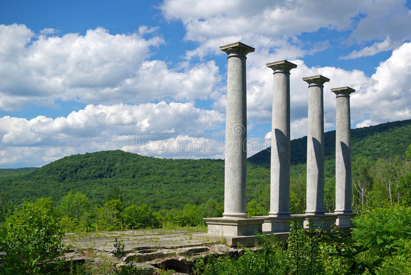 Four pillars. Approaching four pillars from the ruins of an old mansion stock image