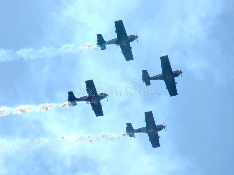 Four piston propeller aerobatic aicraft against sun. royalty free stock photo
