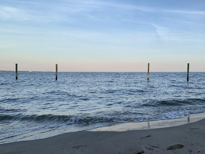 Four Poles In Bay - Beach View. Sky at dusk. Four poles jut out of the water as the waves roll in. Horizon line on the bay royalty free stock images