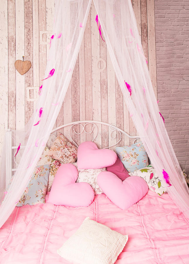 Four-poster bed with pink pillows stock images
