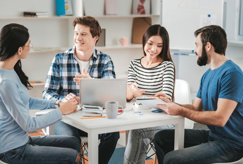 Four postgraduates preparing for international competition. Four postgraduates. Four smart creative postgraduates feeling excited while preparing for royalty free stock images