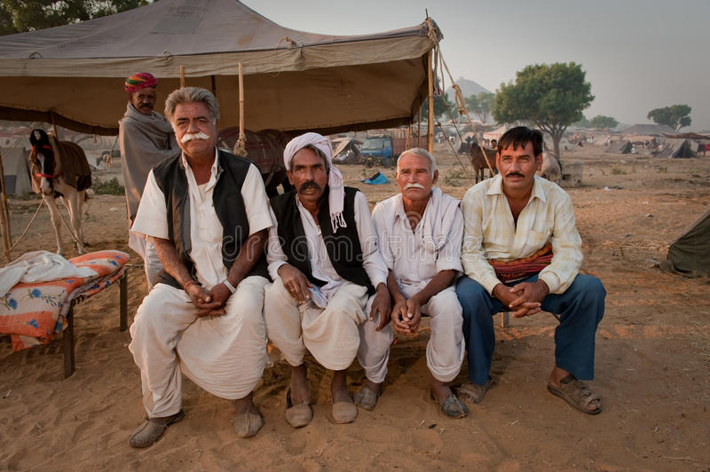 Four rajasthani men on a bed. A group of four rajasthani men sitting on a bed in the morning at the Pushkar Camel Fair 2009 royalty free stock photography
