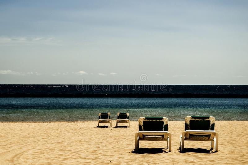 Four reclining chairs on a beach (contrast) stock images