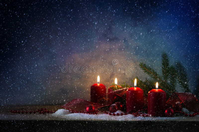 Four red advent candles burning in the snow on a rustic wooden b. Oard, christmas decoration with fir branches, baubles and a gift ribbon against a blue vintage royalty free stock photos