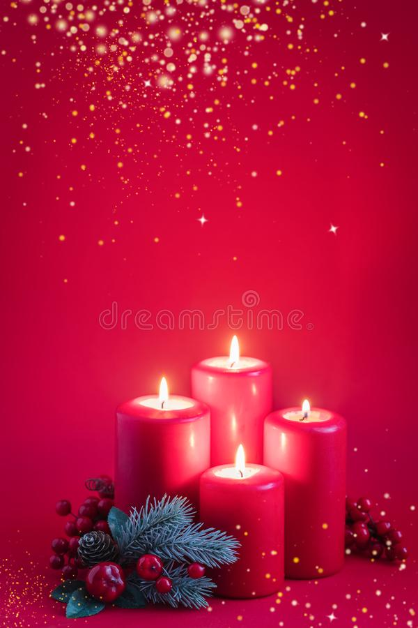 Four red burning advent candles, golden snowflakes and a green spruce branch on a red background. Toned royalty free stock photography
