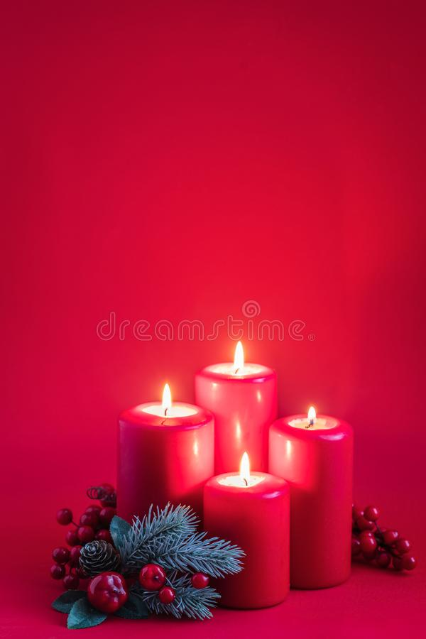 Four red burning advent candles, a green spruce branch on a red background. Toned stock image