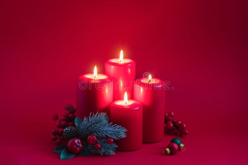 Four red burning advent candles, a green spruce branch on a red background, invitation or postcard concept. Four red burning advent candles, a green spruce stock photography