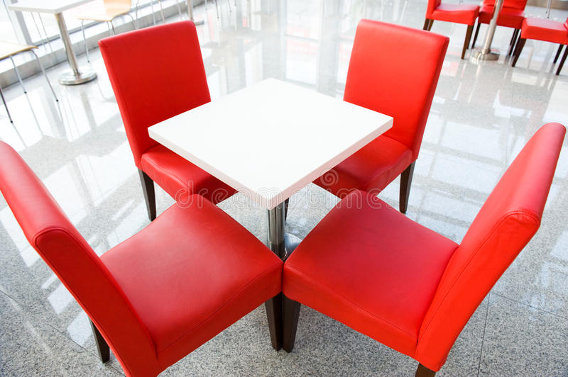 Four red chairs at a table. Above view of white table with four red chairs near by royalty free stock photography