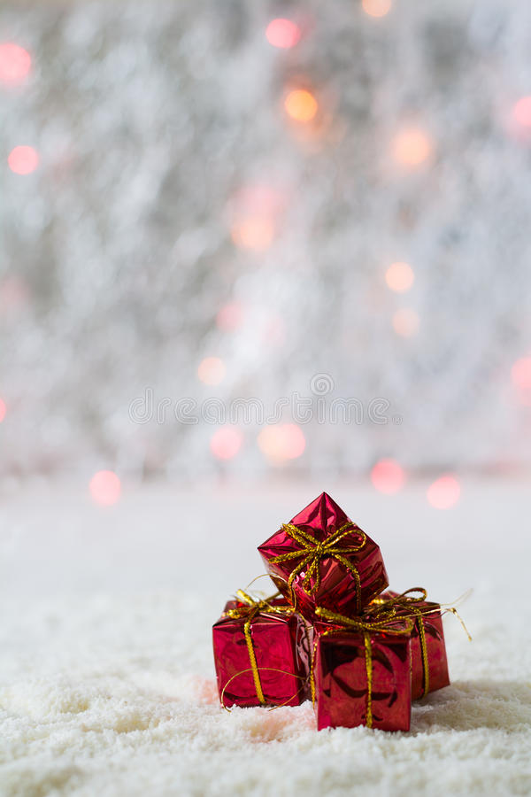 Four red gift boxes on the background of bokeh and snow. Selective focus royalty free stock photo