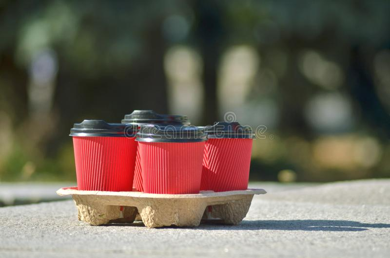 Four red paper coffee cups with black lids on a stand stand on a concrete surface on blurred background of green trees royalty free stock images