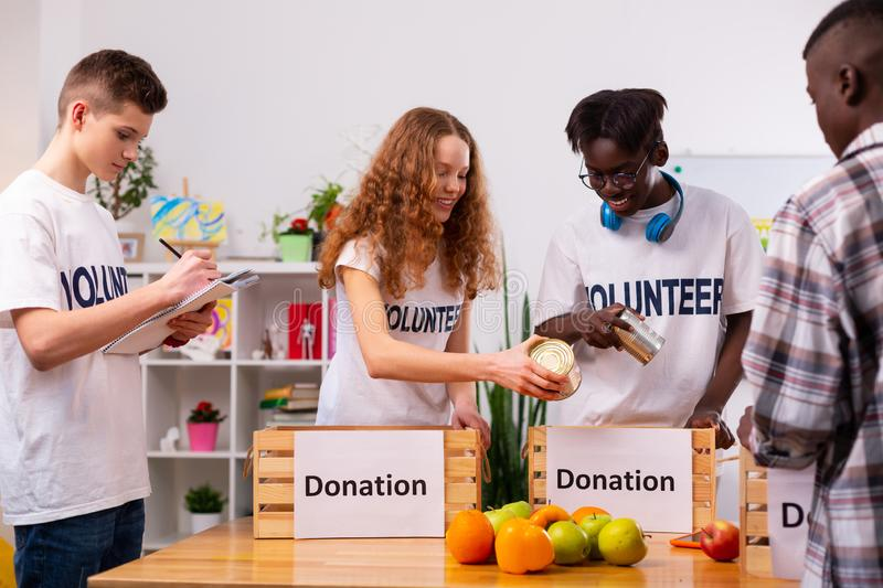 Four responsible teenagers putting food into boxes for donation. Donation time. Four responsible teenagers in white t-shirts putting food into boxes for donation stock photos
