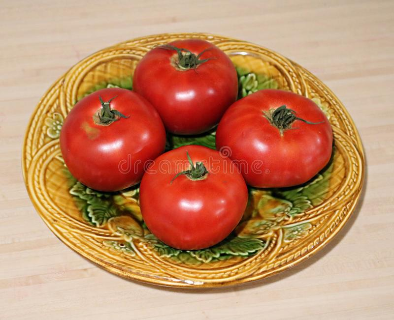 Four ripe tasty red tomatoes on a ceramic decorative plate in the village royalty free stock images