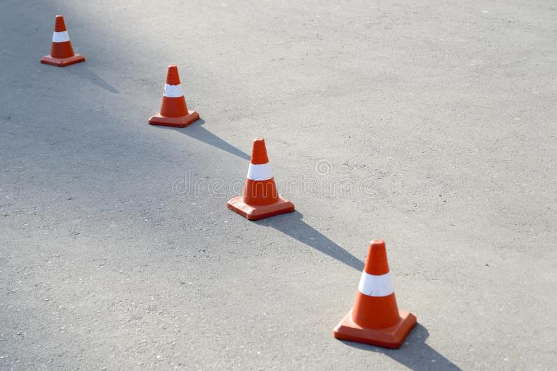 Four road cones on the pavement. Cast a shadow on the sun stock photography