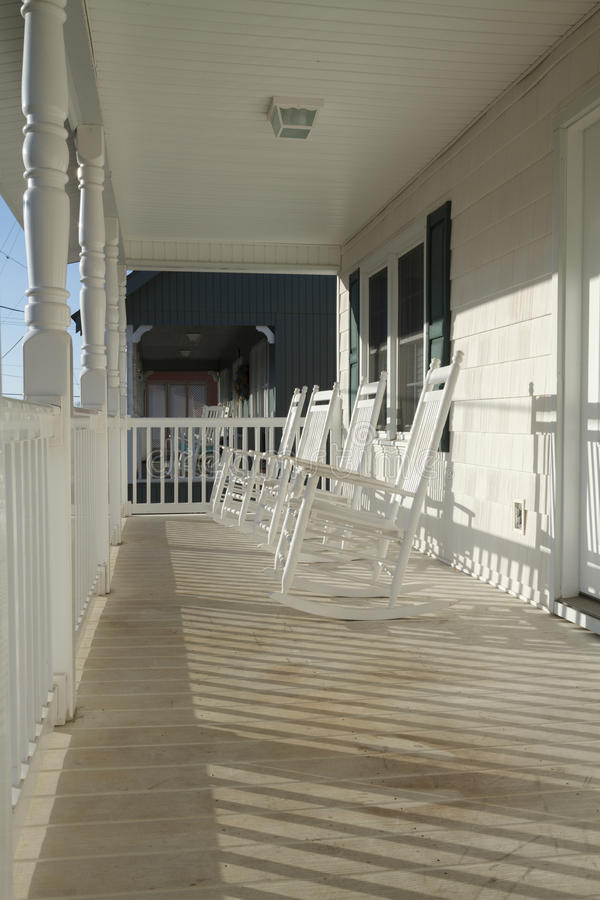 Four Rocking Chairs On A Porch At Sunrise stock image