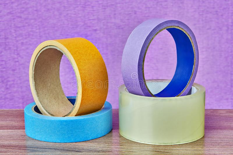 Four rolls of adhesive tape lying on table, lilac background. royalty free stock photos