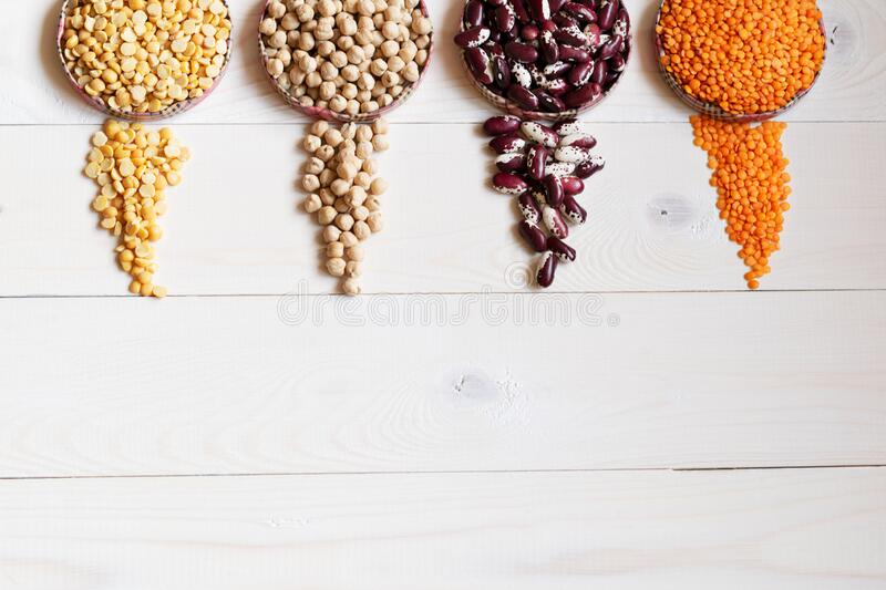 Four round containers with legume crops peas, nut, beans, red lentils on a white wooden background. Top view. Copy space stock image