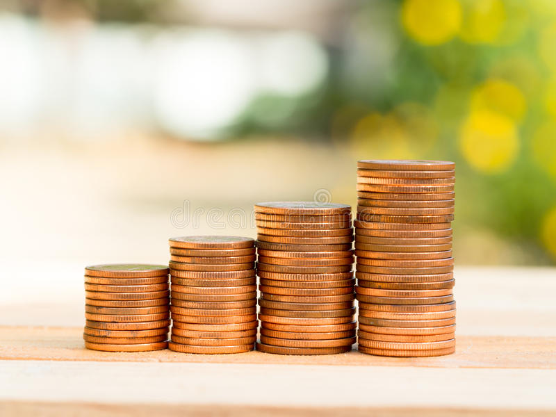 Four rows of rising growth golden stack coins with green nature background. Growing and saving money concept royalty free stock images