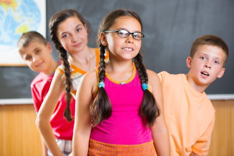 Four schoolchildren standing in classroom against blackboard royalty free stock image