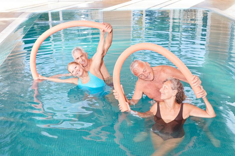 Four seniors in aqua fitness course. Four seniors in the Aquafitness class do exercises with the swimming noodle stock image