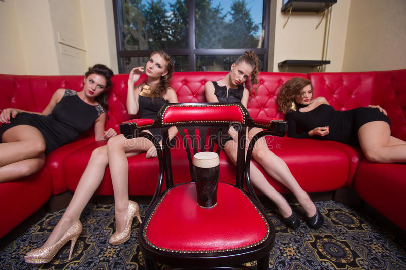Four girls on a red couch. in the interior royalty free stock photography