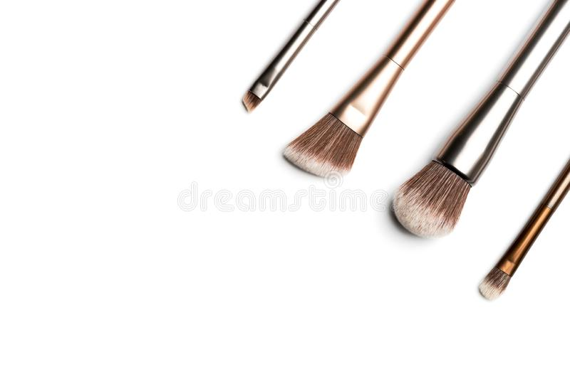 Four shiny bronze- and silver-coloured makeup brushes for applying powder, eyeshadow, eyeliner, bronzer and highlighter arranged. In the corner and shot from royalty free stock image