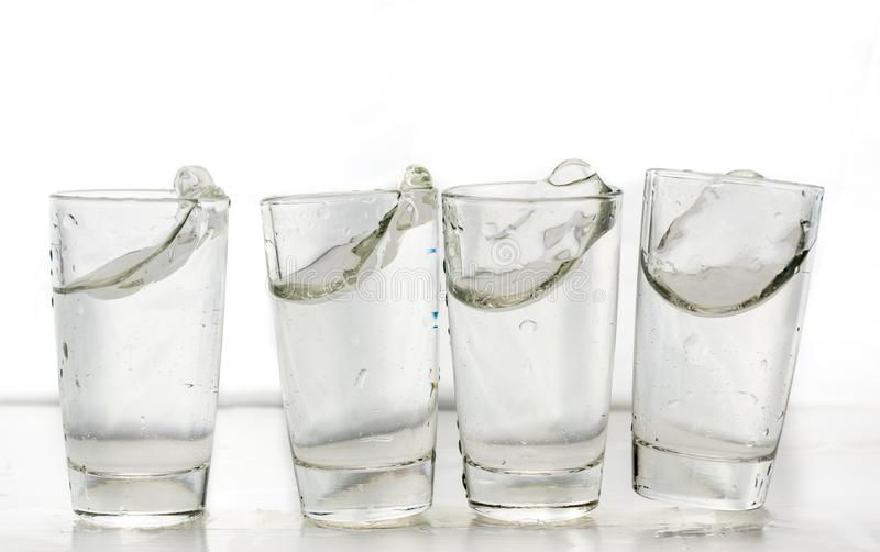 Four shot glasses close up with a splash of water in them and flying water over them.  royalty free stock image