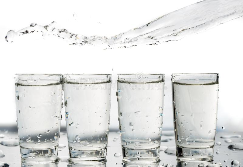 Four shot glasses close up with a splash of water in them and flying water over them.  stock photography