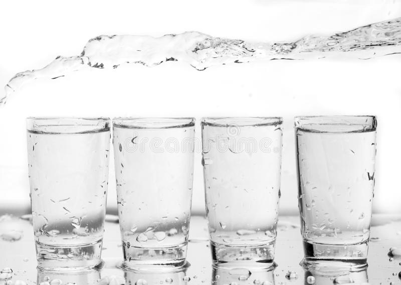 Four shot glasses close up with a splash of water in them and flying water over them royalty free stock images